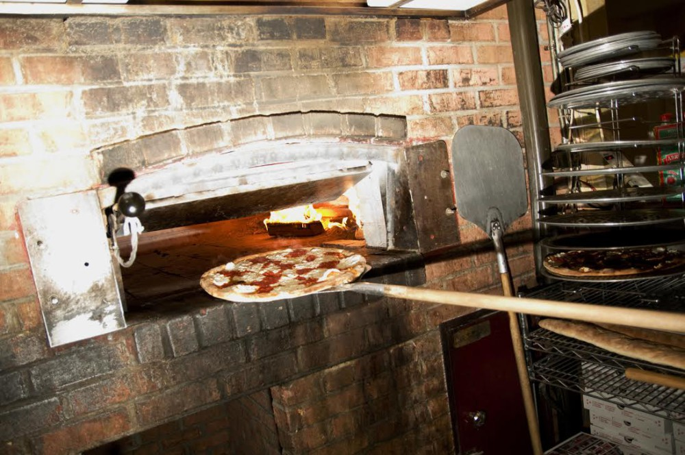 A plain Margherita pie coming out of the wood-burning coal oven at Peppino's