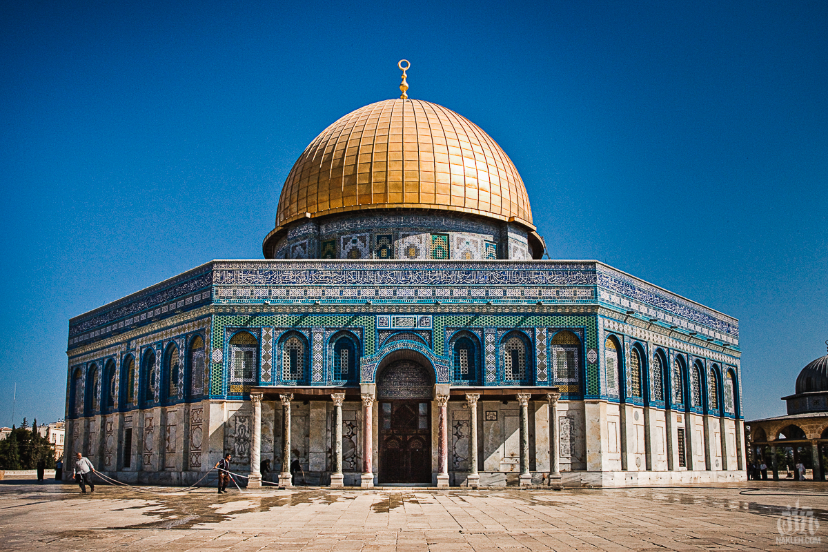 "Dome of the Rock, Jerusalem - After one walking from one of the Old City to the other, on the complete opposite side we came across the Dome of the Rock. One of Islam's highest holy places. It sits on top of the Wailing Wall, one of Israel's highest holy places. Needless to say security there is VERY tight- from both sides. I made my way towards the Mosque with my wife, when she was stopped. ""You are not dressed appropriately. Cover yourself"". She had a tee shirt with a cardigan sweater covering her shoulders, but apparently that wasn't enough. ""It's fine,"" she told me. ""I'll wait here. Go take your pictures"". With a breath and a sigh, I made my way up, alone, took this photograph, and made my way back down to her. I had been there many times before, but I wanted to show her. I never got the chance."